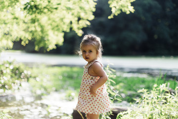 Portrait of little girl standing outdoors during summer