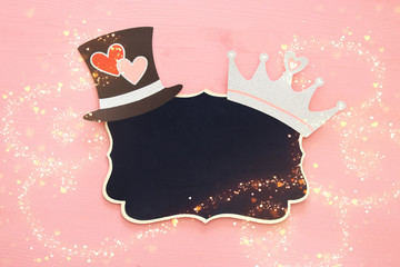 top view image of silver glitter crown, blackboard and hat over pink wooden background.