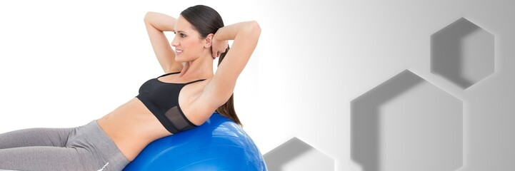 Fit athletic woman in gym with Hexagons and exercise ball