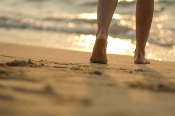 leg a girl walking on the beach with sunset light by walk barefoot