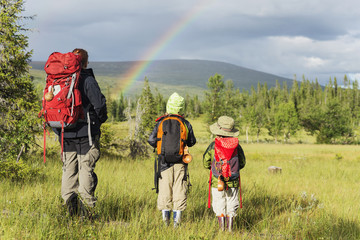 Mother hiking with children and looking at rainbow
