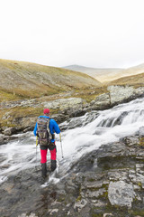 Hiker walking in rapids in mountain region