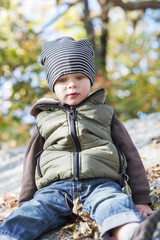 Toddler sitting on rock in warm clothing