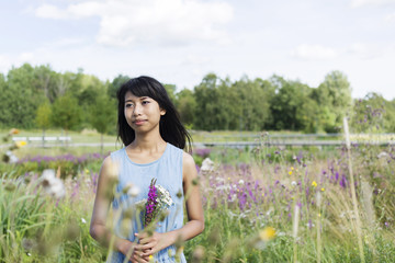 Young woman holding wildflowers in meadow