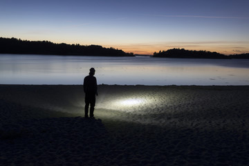 Silhouette of man with flashlight on beach at sunset