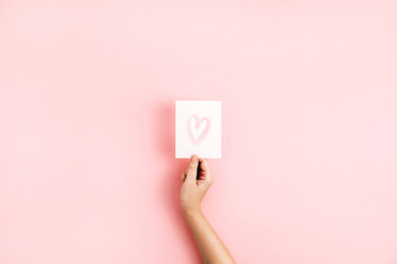 Valentine's Day composition. Female hand holding card with heart symbol on pale pink background. Flat lay, top view Love concept.