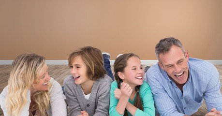 Family laughing together having fun with orange wall in room