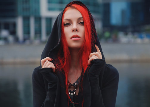 pretty slim red haired alternative girl walking in the city park alone