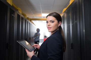 Female engineer working on a tablet computer in server room