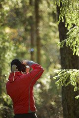 Photographer taking picture in forest