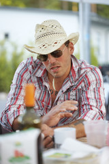 Man dressed as cowboy sitting at table