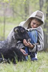 Young kneeling boy caressing black sheep in park