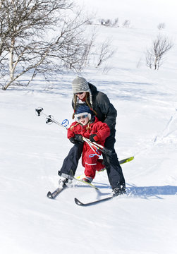 Young woman on skis carrying child on skis in mountain region