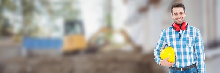 Construction Worker on building site holding helmet