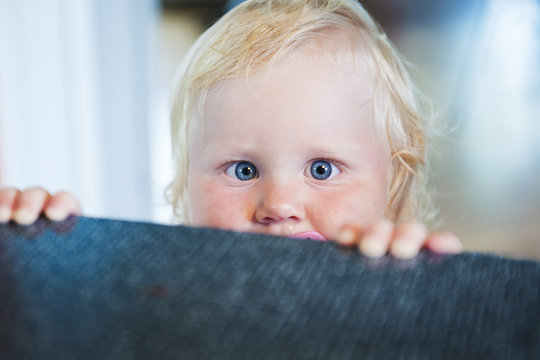 Young baby child peeking head above couch
