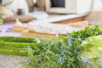 Fresh greens, dill, parsley, lettuce, and cucumbers on the kitchen background. Copy space