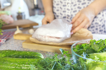 Fresh greens, dill, parsley, lettuce, and cucumbers on the kitchen table. Woman unpacking groceries out of focus. Shallow depth of field. Copy space