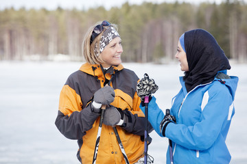 Two female skiers talking outdoors