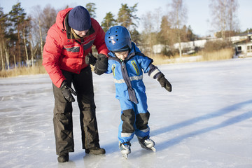 Mother helping boy ice skating on frozen lake or river