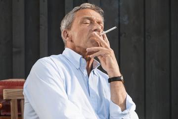Senior man wearing shirt smoking cigarette