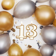 Birthday celebration number 13 candle with gold and silver balloons