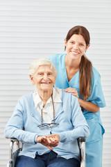 Junge Krankenschwester und lächelnde Seniorin