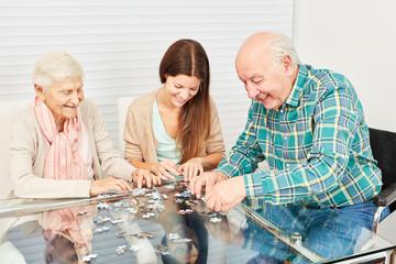 Senioren und Enkeltochter beim Puzzle spielen