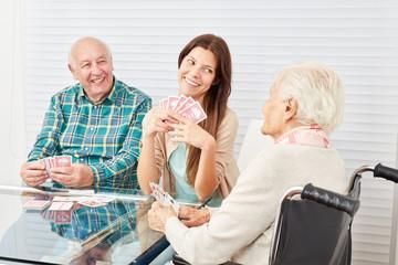 Senioren beim Karten spielen mit Enkeltochter