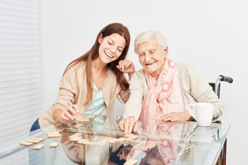 Seniorin spielt mit einer Pflegehilfe Domino
