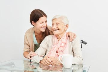 Pflegedienst Frau umarmt Seniorin beim Hausbesuch