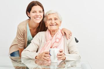 Junge Frau als Altenpfleger betreut eine Seniorin