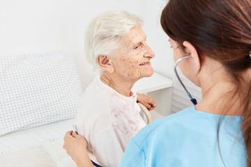 Pflegekraft untersucht alte Patientin