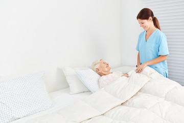 Altenpfleger kümmert sich im Hospiz um Seniorin