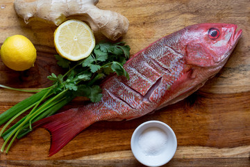Raw whole fresh Red Snapper displayed on a cutting board, seasoned and ready to be steamed.