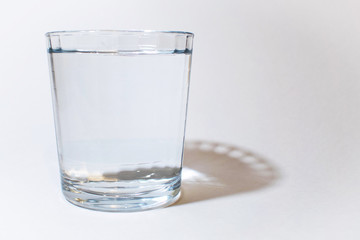 One glass of water on white with shadow