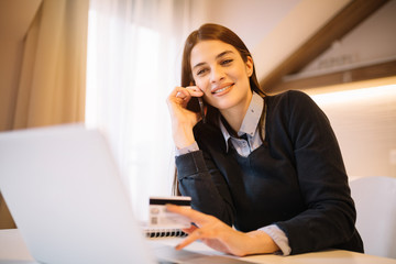 Young charming businesswoman holding a credit card and talking on mobile while working from home.