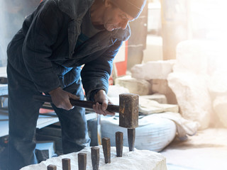 The sculptor of the stone-maker strikes with a heavy hammer on wedges clogged in a marble block.
