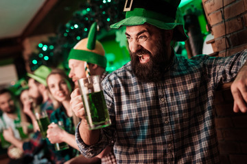 The guy in the cap of the leprechaun is drinking beer. Wall mural