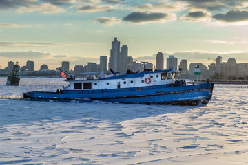 Tugboat breaking ice in a harbor with city skyline in background