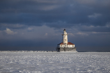 Lighthouse at edge of frozen harbor