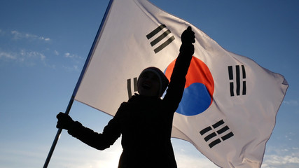 Girl cheerleader with South Korean flag rejoices and supports athletes