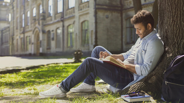 Mixed-race guy sitting under tree in park, reading book, leisure time, hobby