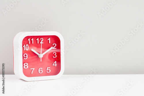 Red alarm clock with white frame show 10:20 on white table and grey ...