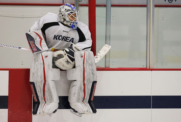 South Korean women's ice hockey goaltender So Jung Shin sits on the boards during practice in Hamden