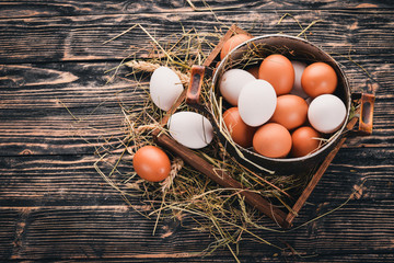 Chicken eggs in a metal saucepan. On a wooden background. Top view. Copy space.