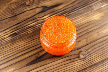 Red caviar in glass jar on wooden table