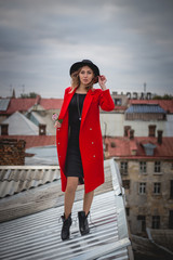 Girl in red posing on the roof of old city