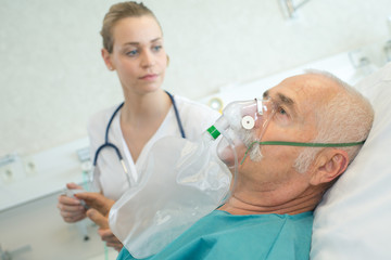 close-up of senior man using oxygen mask in clinic