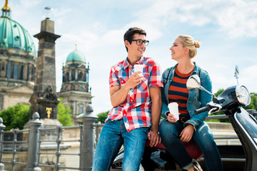 Tourists, woman and man, on scooter trip in Berlin taking a rest on the Museum Island