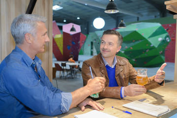 two mature man sitting at rock climbing bar with beer